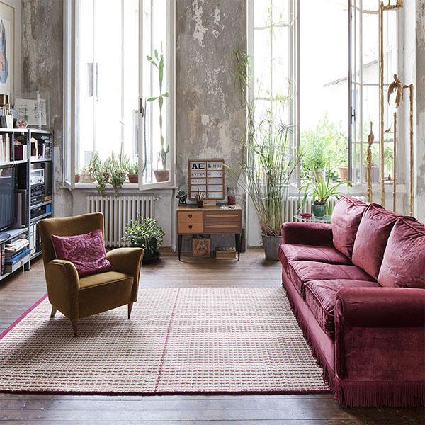 Salotto arredato con divano in velluto rosso e tappeto in contrasto