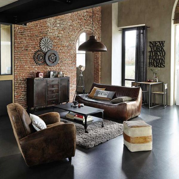 Soggiorno indurstriale con pareti in mattoni, divani in pelle vintage, tappeto e pouf in tessuto