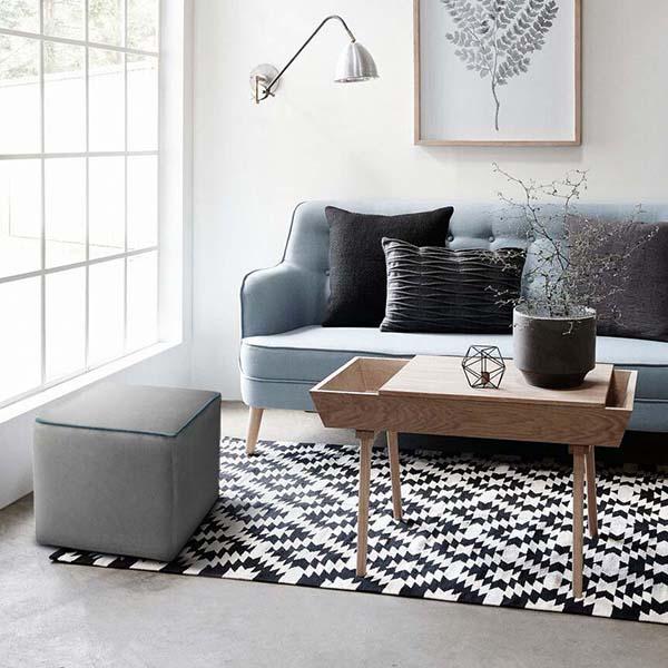 Arredamento in stile nordico con pouf e divano in tessuto grigio e bordo blue. Completa la stanza un tavolino in legno,