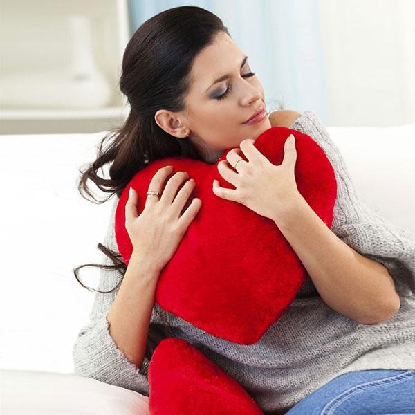 Ragazza sul divano con tra le braccia un cuscino a forma di cuore rosso