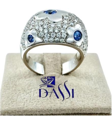 Anello a fascia in oro bianco con pave di diamanti  e inserti  a forma di fiore con al centro zaffiri