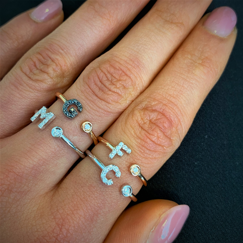 Anelli in oro con punto luce e lettera con diamanti